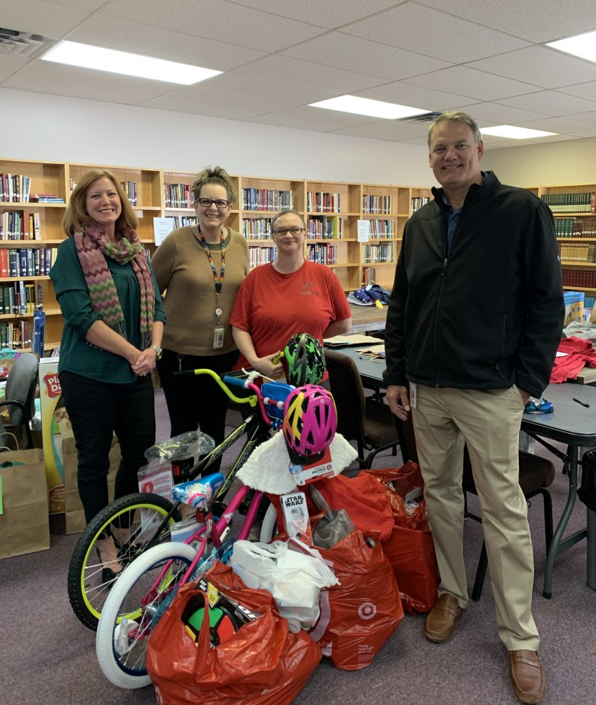 4 people with donated bikes and toys